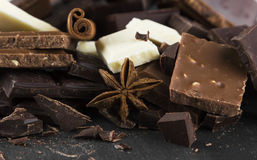 Pedazos de diverso chocolate con las especias en un fondo oscuro imagen de archivo libre de regalías