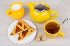 Pedazos de empanada de la torta dulce, de jarro de leche y de té en la tabla Imagenes de archivo