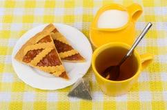 Pedazos de empanada, de té y de leche de la torta dulce en mantel Fotografía de archivo