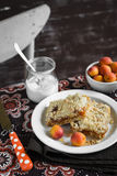 Pedazos de empanada del albaricoque en una placa blanca, el cuenco con los albaricoques y un tarro de yogur natural en la tabla Fotografía de archivo libre de regalías