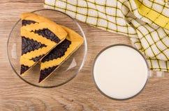 Pedazos de empanada del arándano en el platillo transparente, taza de leche Imagenes de archivo