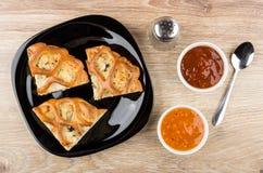 Pedazos de empanada en placa, salsas, pimienta y cuchara Imagen de archivo libre de regalías