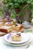 Pedazos de empanada de la fruta con los pedazos de ciruelos y de melocotón y de un ramo de flores en una tabla de madera Estilo r Fotos de archivo