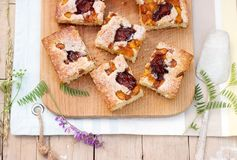 Pedazos de empanada de la fruta con los pedazos de ciruelos y de melocotón y de un ramo de flores en una tabla de madera Estilo r Imagen de archivo