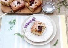 Pedazos de empanada de la fruta con los pedazos de ciruelos y de melocotón y de un ramo de flores en una tabla de madera Estilo r Imágenes de archivo libres de regalías