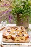 Pedazos de empanada de la fruta con los pedazos de ciruelos y de melocotón y de un ramo de flores en una tabla de madera Estilo r Foto de archivo