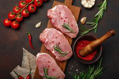 Pedazos de filete crudo del cerdo en tabla de cortar con el mortero de los tomates de cereza, del romero, del ajo, de la pimienta foto de archivo