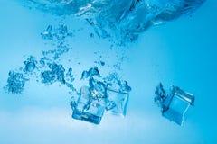 Pedazos de hielo en agua Imagen de archivo