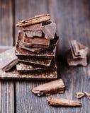 Pedazos de la barra de chocolate Fondo con el chocolate Concepto dulce de la foto de la comida Los pedazos del chocolate quebrado Foto de archivo libre de regalías