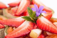 Pedazos de la fresa encima de la ensalada de frutas Imagen de archivo libre de regalías
