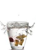 Pedazos de la piña que caen en agua Imagen de archivo libre de regalías