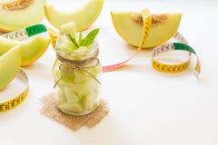 Pedazos de melón en un tarro y un centímetro Imagen de archivo libre de regalías