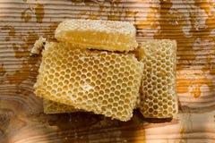 Pedazos de miel fresca de la abeja en panales en una tabla rústica Foto de archivo