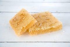 Pedazos de miel fresca de la abeja en panales en una tabla rústica Imagen de archivo libre de regalías