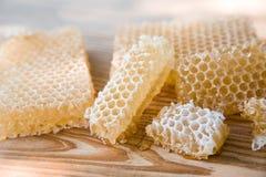 Pedazos de miel fresca de la abeja en panales en una tabla rústica Foto de archivo libre de regalías