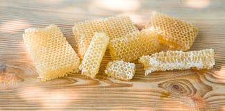 Pedazos de miel fresca de la abeja en panales en una tabla rústica Fotografía de archivo