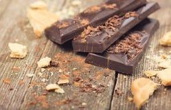 Pedazos de migas del chocolate y de las galletas en viejos tableros Foto de archivo