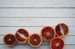 Pedazos de naranja de sangre en fondo de madera foto de archivo