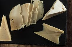 Pedazos de opinión superior del queso un fondo de la pizarra y de la madera naturales Foto de archivo libre de regalías