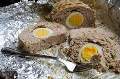 Pedazos de pan con carne con el huevo en una hoja Foto de archivo libre de regalías