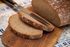 Pedazos de pan en el tablero para cortar el pan Imagen de archivo libre de regalías