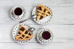 Pedazos de pastel de calabaza fragante en una tabla de madera con las tazas de café fotos de archivo