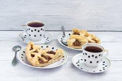 Pedazos de pastel de calabaza fragante en una tabla de madera con las tazas de café imagen de archivo