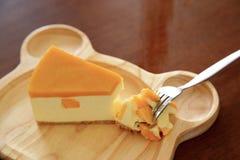 Pedazos de pastel de queso del mango en la placa de madera Fotografía de archivo