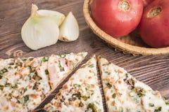 Pedazos de pizza, de cebollas blancas y de tomates Imágenes de archivo libres de regalías