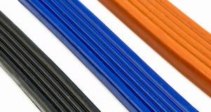 3 pedazos de plasticine anaranjados, de azul y de negro Fotografía de archivo