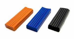 3 pedazos de plasticine anaranjados, de azul y de negro Imagenes de archivo