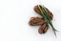 Pedazos de plumas del pan oscuro hecho en casa y de la cebolla verde en un fondo blanco imagenes de archivo