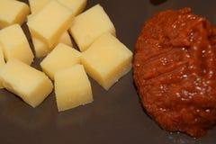 Pedazos de queso con la salsa de barbacoa Fotos de archivo libres de regalías