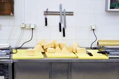 Pedazos de queso en la tabla del corte en tienda Fotos de archivo