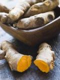 Pedazos de raíz de cúrcuma fresca entera y agrietada Foto de archivo