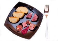 Pedazos de rebanadas del salami y del pan en plato desde arriba Foto de archivo libre de regalías