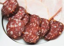 Pedazos de salchicha ahumada en una placa. Comida nutritiva Fotografía de archivo libre de regalías