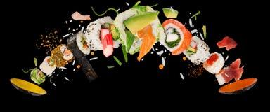 Pedazos de sushi japonés delicioso congelado en el aire imagen de archivo