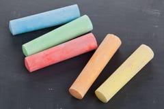 Pedazos de tiza coloridos en la pizarra Imagenes de archivo