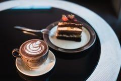 Pedazos de torta Café del cacao del chocolate caliente de la bebida en tazas Fondo negro Foto de archivo