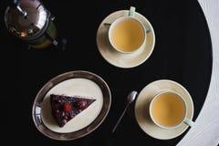 Pedazos de torta Café del cacao del chocolate caliente de la bebida en tazas Fondo negro Foto de archivo libre de regalías