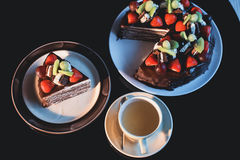 Pedazos de torta Café del cacao del chocolate caliente de la bebida en tazas Fondo negro Imagen de archivo libre de regalías