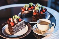 Pedazos de torta Café del cacao del chocolate caliente de la bebida en tazas Fondo negro Fotos de archivo libres de regalías