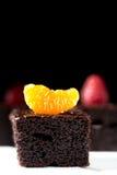 Pedazos de torta de chocolate oscura adornada con la mandarina Imagen de archivo