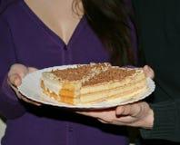 Pedazos de torta en una placa en las manos de un par cariñoso Foto de archivo