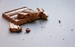 Pedazos del chocolate con leche con las avellanas y las pasas machacadas con alcohol en fondo negro Degustation de la confitería imagen de archivo