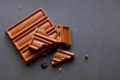 Pedazos del chocolate con leche con las avellanas y las pasas machacadas con alcohol en fondo negro Degustation de la confitería foto de archivo libre de regalías