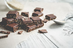 Pedazos del chocolate con sésamo en una tabla Foto de archivo