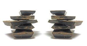 Pedazos del chocolate en blanco Imagen de archivo
