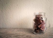 Pedazos del chocolate en la botella de cristal Imágenes de archivo libres de regalías
